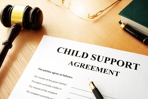 Child support agreement with pens, a gavel, glasses, and a book.