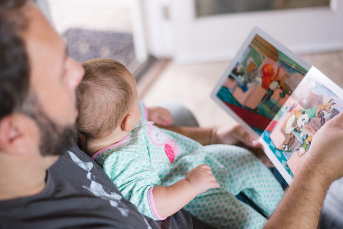 Man with a baby in his lap, reading a children's book.